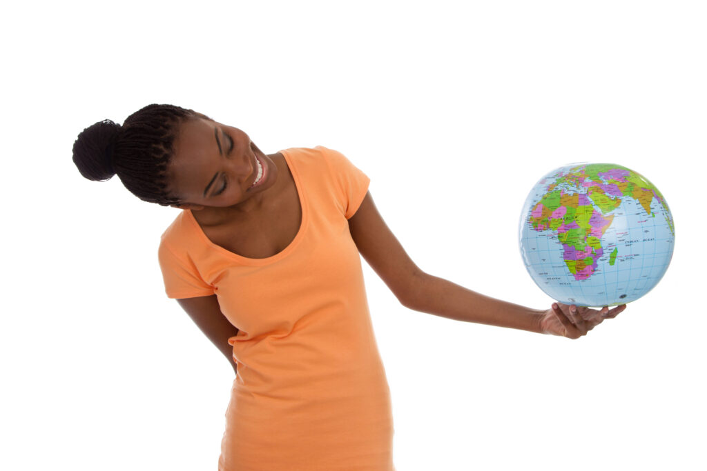 A Black female student holds a globe and considers where she will study.