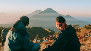 Two guys admiring a mountain at sunrise