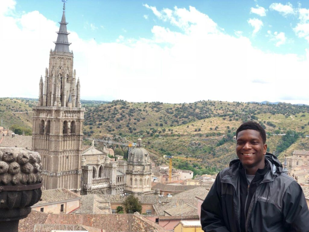 The author stands in front of a view of a cathedral tower and the Spanish countryside