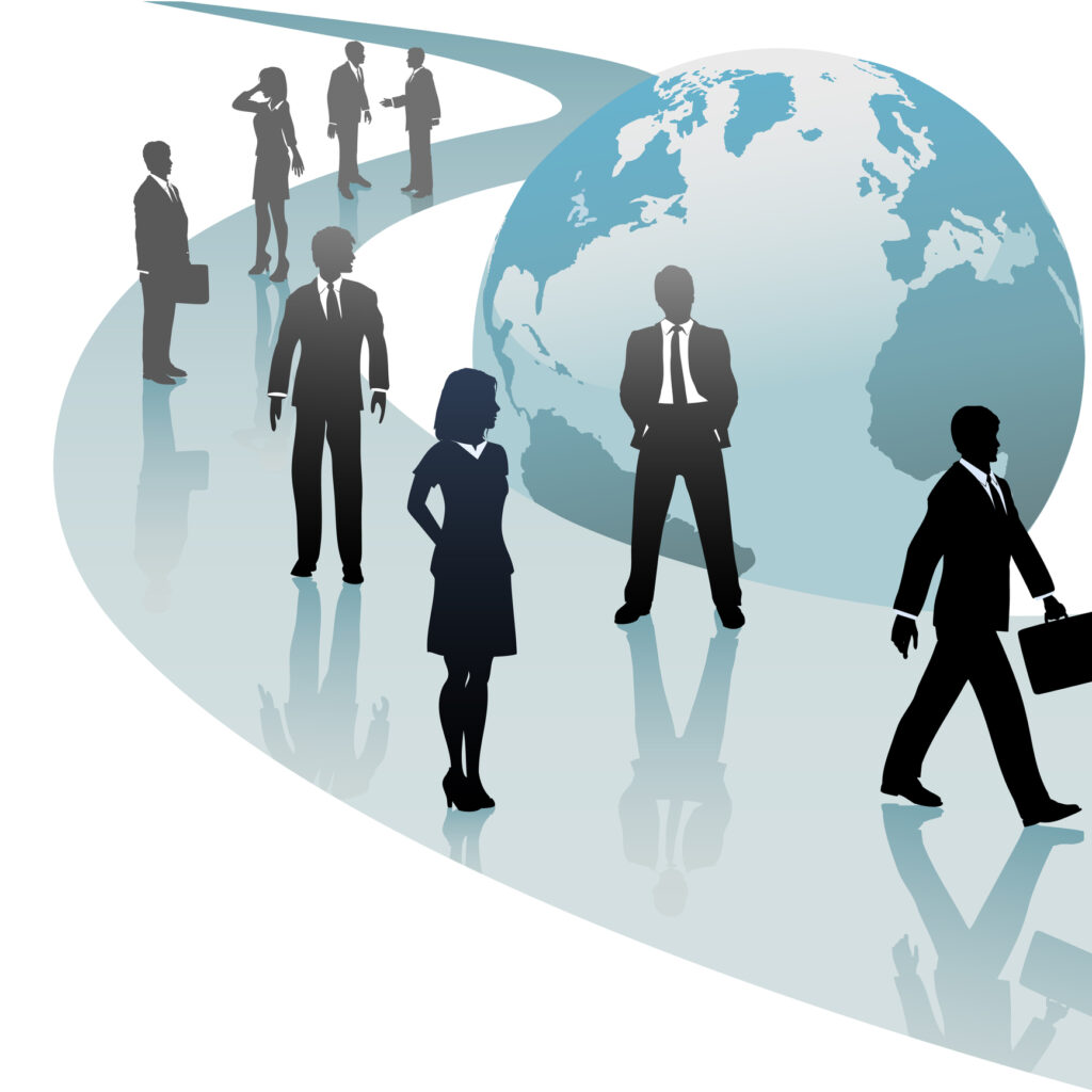Silhouetted business people stand and walk along a path next to a globe of the planet